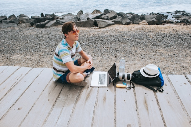Hübscher junger kerl der fotograf, der mit einem laptop am strand arbeitet