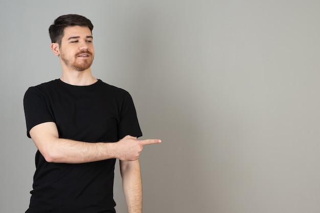 Hübscher junger kerl, der mit dem finger auf grau zeigt.