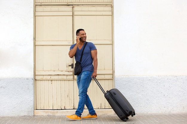 Hübscher junger kerl des vollen körpers, der mit koffer geht und am handy spricht