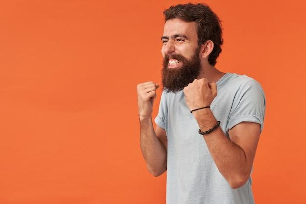 Hübscher junger kerl mit arm in faust emotion gewinnen highscore-spieler-gewinner posiert, stehend