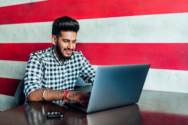 Hübscher, junger, lächelnder afrikanischer mann in der abendgarderobe, der seinen laptop benutzt, während er sich an der bar lehnt.