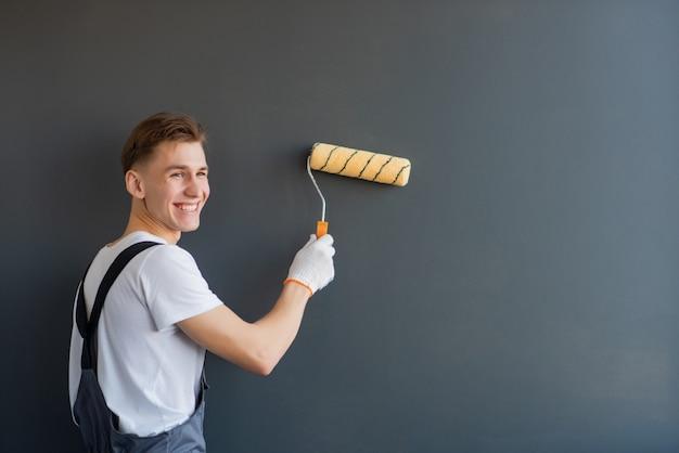Hübscher junger lächelnder arbeiter mit farbroller auf grauem hintergrund