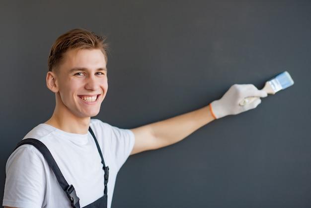 Hübscher junger lächelnder arbeiter mit pinsel auf grauem hintergrund