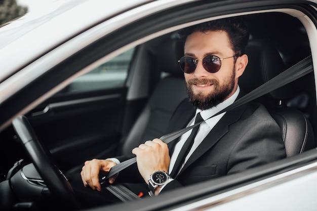Hübscher junger lächelnder bärtiger fahrer im vollen anzug mit sicherheitsgurt, der ein auto fährt