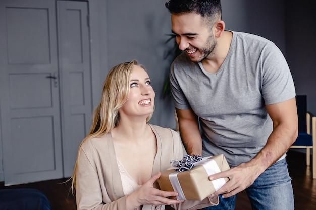 Hübscher junger lächelnder mann gibt seiner reizenden freundin zu hause ein geschenk