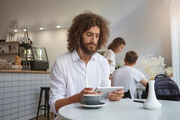 Hübscher junger lockiger mann mit bart, der am tisch im café mit tablette in den händen sitzt, ernsthaft auf dem bildschirm schaut und kopfhörer trägt und über stadtcafé aufwirft