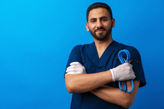 Hübscher junger männlicher arzt in blauer uniform mit stethoskop vor blauem hintergrund