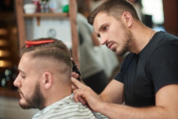 Hübscher junger männlicher friseur, der seinem klienten einen haarschnitt mit einem haarschneider gibt, der in seinem friseursalon arbeitet.