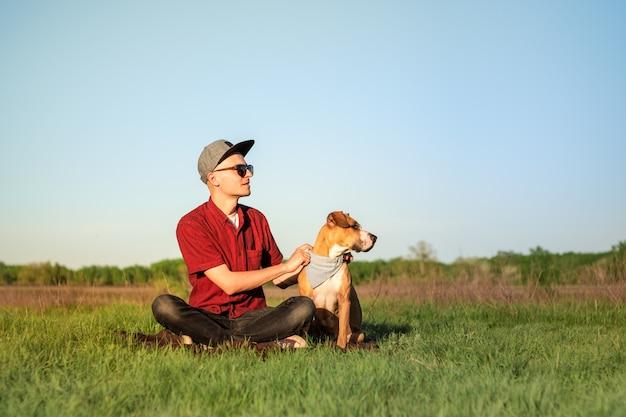 Hübscher junger männlicher hundebesitzer und staffordshire terrier dpg sitzen am rasen