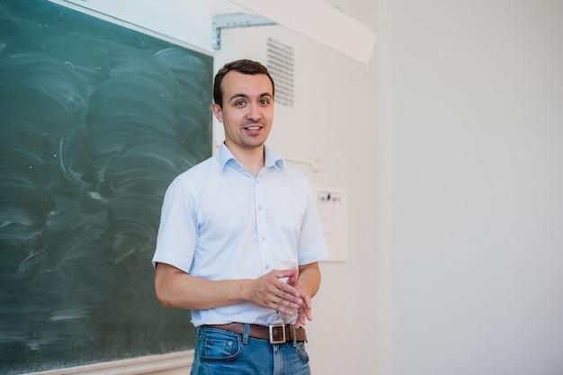 Hübscher junger männlicher schüler oder lehrer, der entspannend gegen eine grüne tafel steht