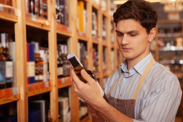 Hübscher junger männlicher sommelier, der an seinem laden arbeitet, etikett auf einer weinflasche liest, raum kopiert