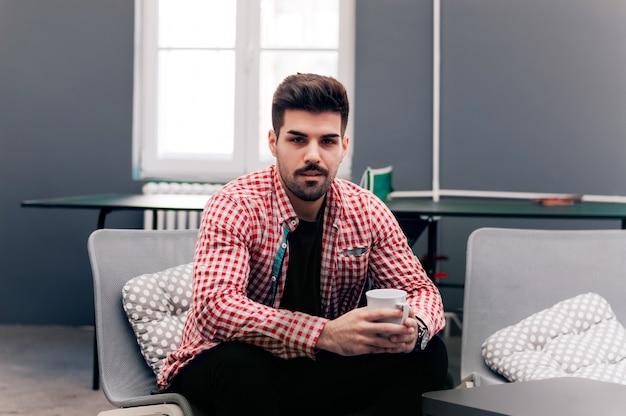 Hübscher junger männlicher student sitzt in seinem innenministerium und hält kaffeetasse.
