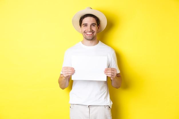 Hübscher junger männlicher tourist im sommerhut lächelnd, leeres blatt papier für ihr zeichen haltend, über gelbem hintergrund stehend