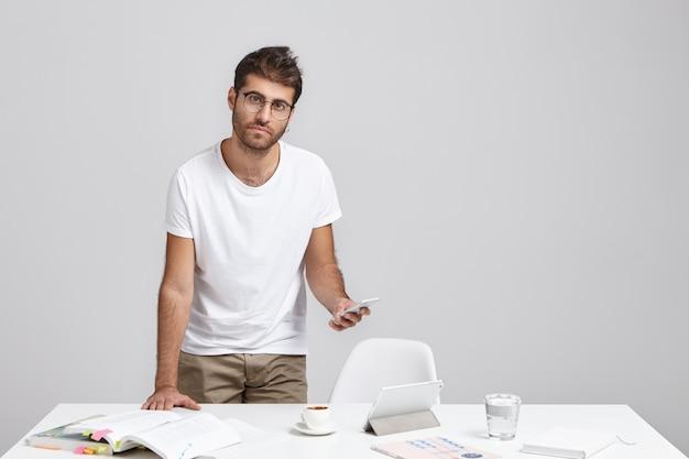 Hübscher junger männlicher wirtschaftslehrer mit stoppeln, die am weißen schreibtisch mit lehrbüchern stehen
