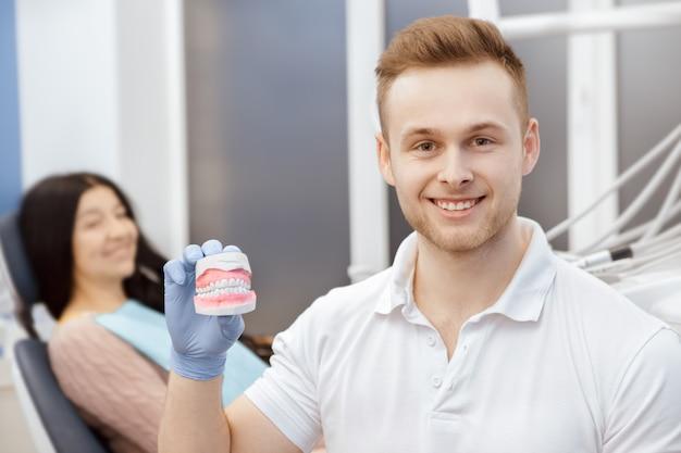 Hübscher junger männlicher zahnarzt, der zahnform demonstriert