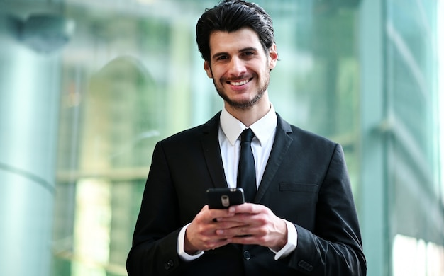 Hübscher junger manager, der ein smartphone im freien verwendet