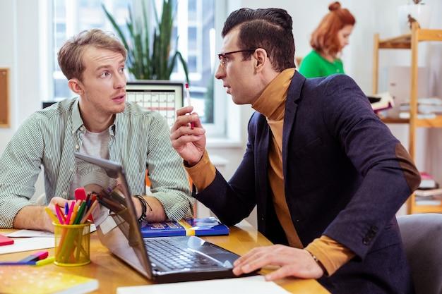Hübscher junger mann bittet seinen studenten um eine quest, während er seinen kollegen fragt