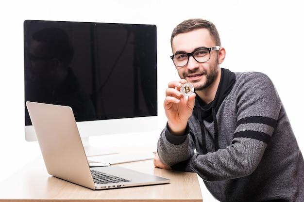 Hübscher junger mann, der am büroplatz mit laptop und bildschirm des monitors auf seinem rücken sitzt, zeigte bitcoin auf weiß
