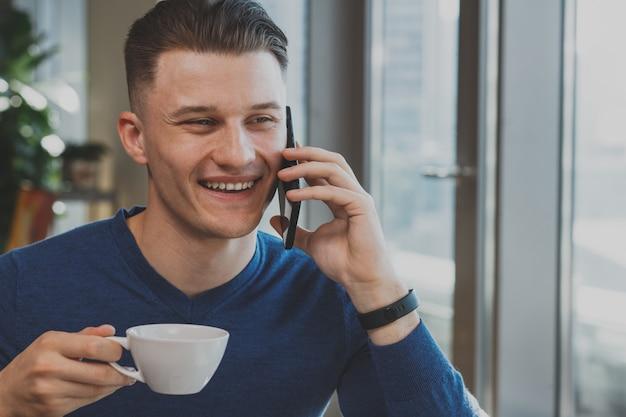 Hübscher junger mann, der am café frühstückt
