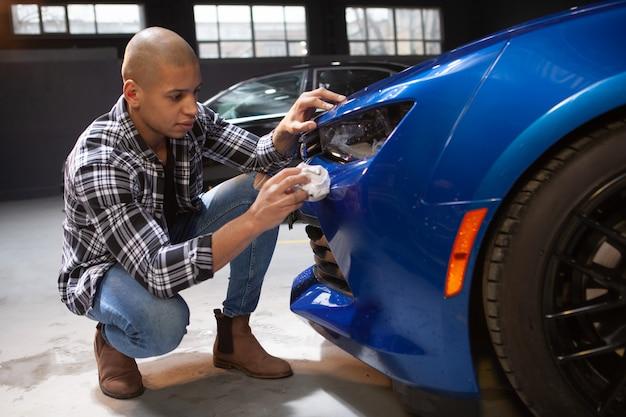 Hübscher junger mann, der an seiner garage arbeitet