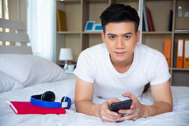 Hübscher junger mann, der auf bett und gebrauch smartphone liegt