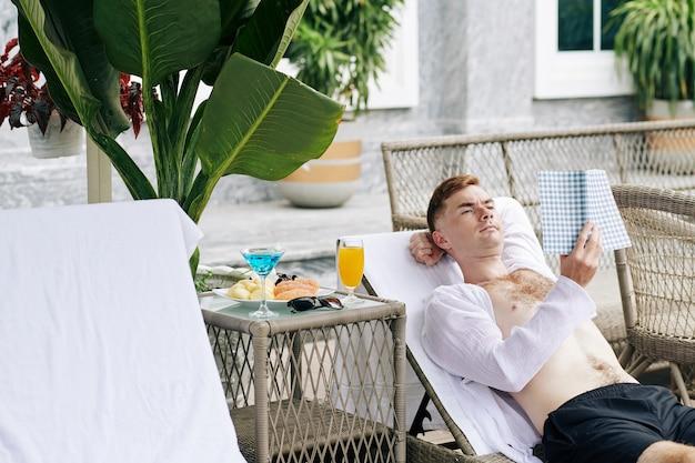 Hübscher junger mann, der auf chaiselongue ruht, frühstück isst und interessantes buch liest