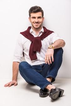Hübscher junger mann, der auf dem boden und dem lächeln sitzt.