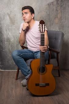 Hübscher junger mann, der auf dem stuhl sitzt, während er gitarre hält.