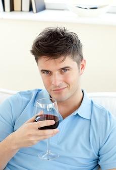 Hübscher junger mann, der auf einem sofa hält weinglas sitzt