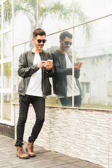 Hübscher junger mann, der auf glaswand unter verwendung des smartphone sich lehnt