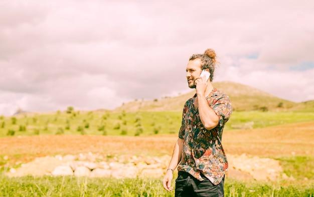 Hübscher junger mann, der auf smartphone in der landschaft spricht