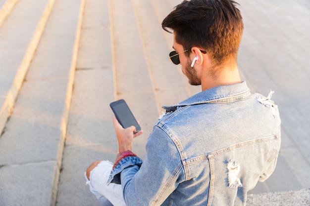 Hübscher junger mann, der auf stufen im freien unter verwendung des mobiltelefons sitzt und musik hört