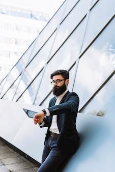 Hübscher junger mann, der aufpassende zeit der digitalen tablette auf armbanduhr hält