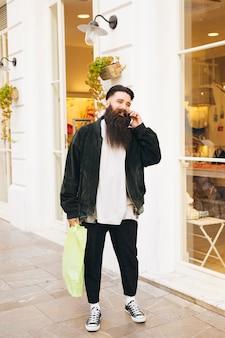 Hübscher junger mann, der außerhalb des shops spricht am handy steht