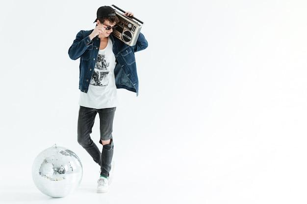 Hübscher junger mann, der boombox nahe discokugel hält