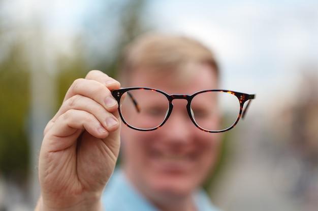 Hübscher junger mann, der brille hält und durch sie schaut