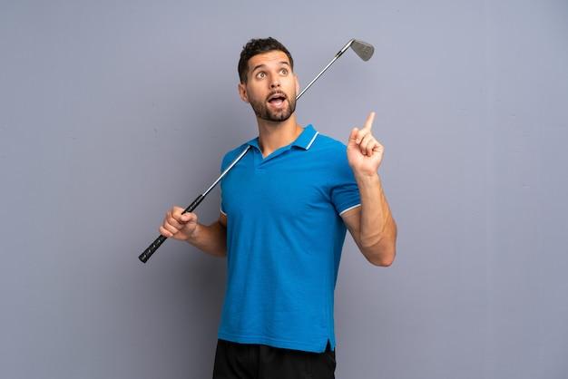 Hübscher junger mann, der das golf beabsichtigt, die lösung beim anheben eines fingers zu verwirklichen spielt