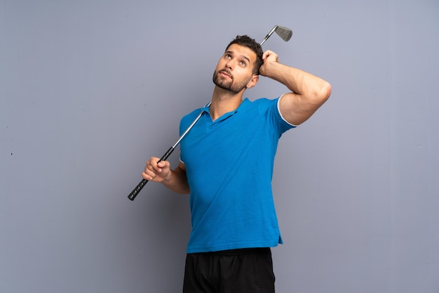 Hübscher junger mann, der das golf hat zweifel und mit verwirren gesichtsausdruck spielt