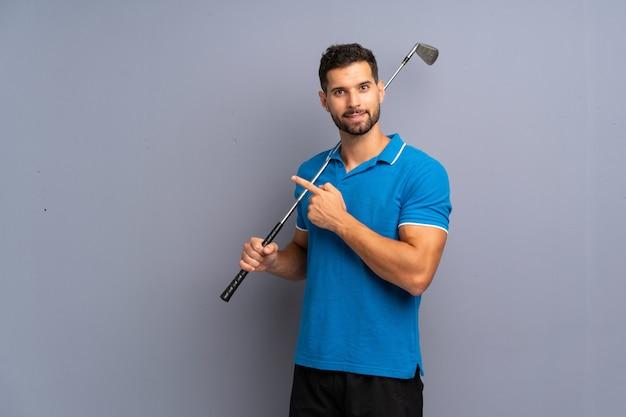 Hübscher junger mann, der das golf zeigt auf die seite spielt, um ein produkt darzustellen