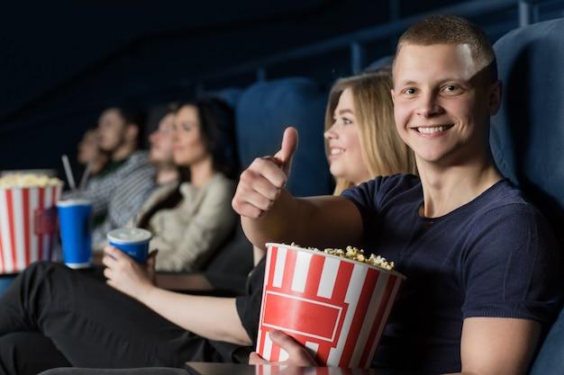 Hübscher junger mann, der daumen einen film am kino oben genießend zeigt