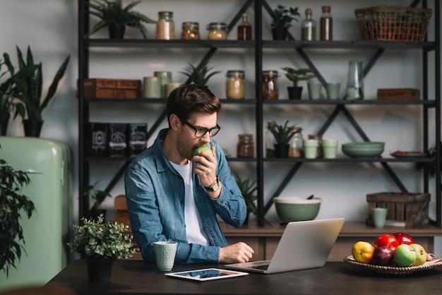 Hübscher junger mann, der den apfel betrachtet digitale tablette in der küche isst