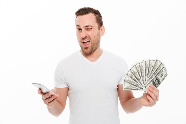 Hübscher junger mann, der den handy hält geld verwendet.