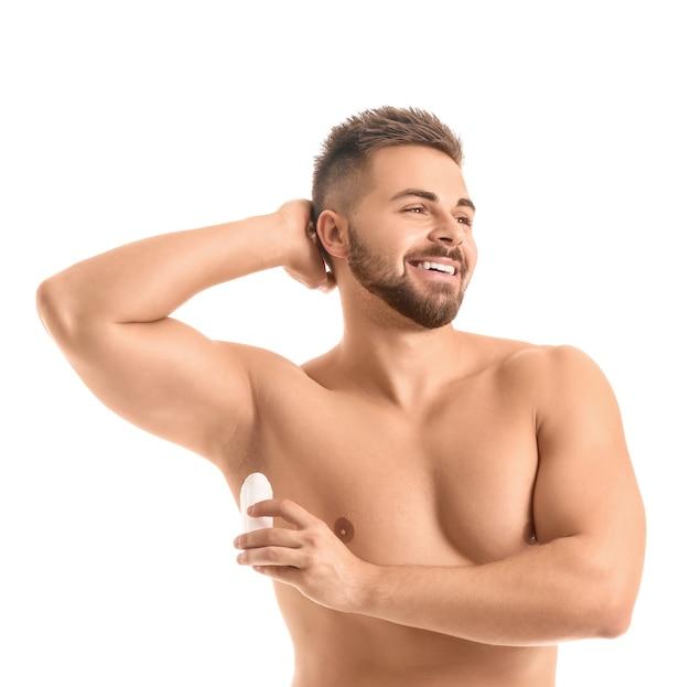 Hübscher junger mann, der deodorant auf weißer oberfläche verwendet