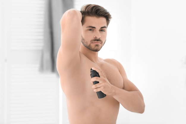 Hübscher junger mann, der deodorant im badezimmer benutzt