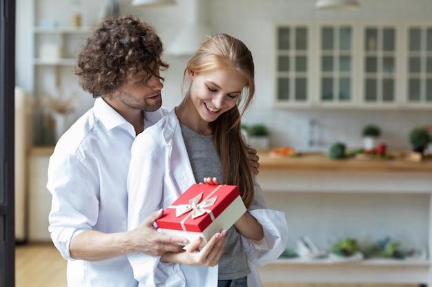 Hübscher junger mann, der der schönen frau zu hause geschenk gibt. glückliches familienkonzept.