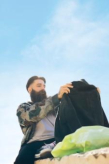 Hübscher junger mann, der die neue jacke sitzt unter dem himmel betrachtet
