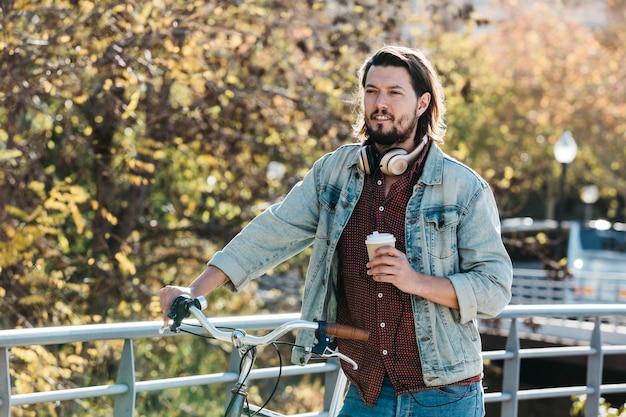 Hübscher junger mann, der die papierkaffeetasse steht mit fahrrad im park hält