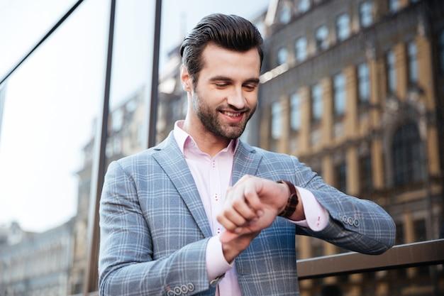 Hübscher junger mann, der die zeit auf seiner armbanduhr überprüft