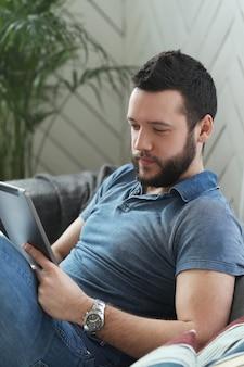 Hübscher junger mann, der digitales tablett oder ebook benutzt