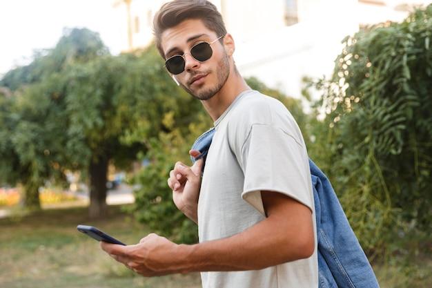 Hübscher junger mann, der draußen geht und musik auf der straße mit handy hört und plaudert
